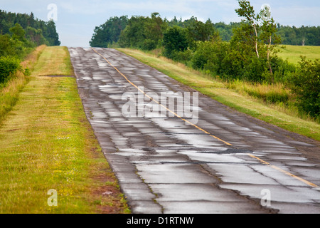 A paved asphalt road broken up from freezing and thawing. Cold patch is in the pot holes and wide cracks. - Stock Photo