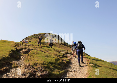 People walking on worn eroded path up Catbells mountain ridge in Lake District National Park on a sunny weekend - Stock Photo