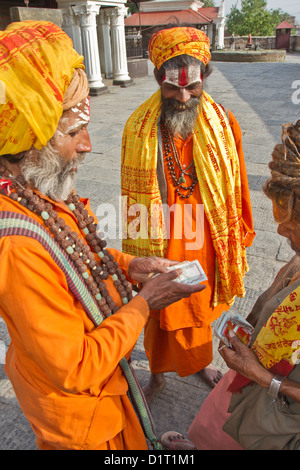 Sadhu holy men counting money at the burning ghats at Pashupatinath temple on the Bagmati River Kathmandu Nepal - Stock Photo