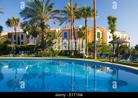 Colònia de Sant Pere, Mallorca, Balearic Islands, Spain. View across pool to luxury apartment complex set amongst - Stock Photo