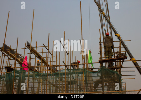 Chinese workers on scaffolding during construction of Huinanzhuang pumping station, China - Stock Photo
