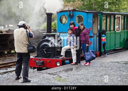 Tourist family having their photo taken at the Llanberis Lake Railway, Llanberis, Gwynedd, North Wales - Stock Photo