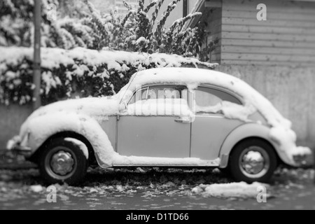 Black and white tilt shift image of an old Volkswagen Bugs sits snow covered on a street in Europe. - Stock Photo