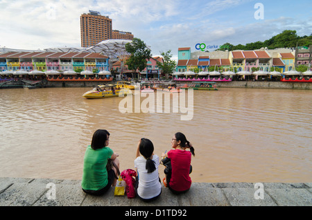 Three women sitting down on the Singapore River bank overlooking the brightly painted entertainment precinct of - Stock Photo