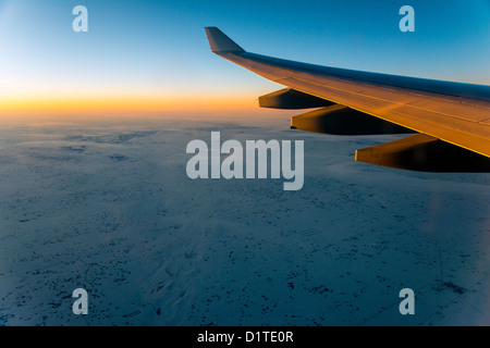 Panoramic view from the plane at sunset over the snowy Saskatchewan province, Canada - Stock Photo
