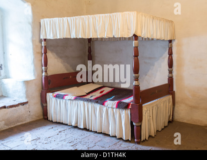 Traditional four poster bed with blanket in old stone floor bedroom - Stock Photo