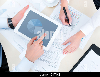 Business people developing a business project and analyzing market data information on a modern digital tablet computer. - Stock Photo