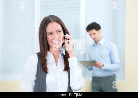 Beautiful young business woman speaks on a mobile phone. Young businessman with digital tablet on the background - Stock Photo
