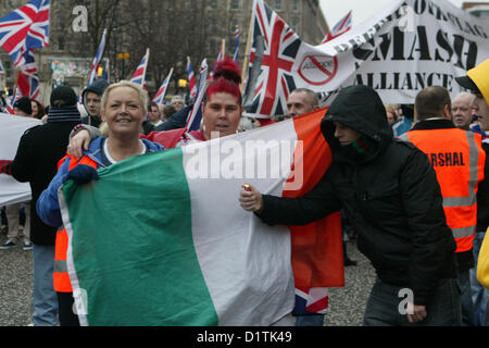 Belfast, UK. 5th Jan, 2013. Two Loyalist women hold an Irish Tricolour flag as a Youth tries to set fire to it during - Stock Photo