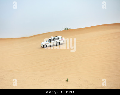 4x4 Jeeps participate in dune-bashing during a desert safari in Dubai, UAE - Stock Photo