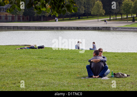 A young couple sit and hug each other in the gardens of the Palace of Versailles, Paris, France - Stock Photo
