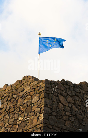 European Union Flag Flying on an Old Stone Building near Bushmills in County Antrim Northern Ireland United Kingdom - Stock Photo