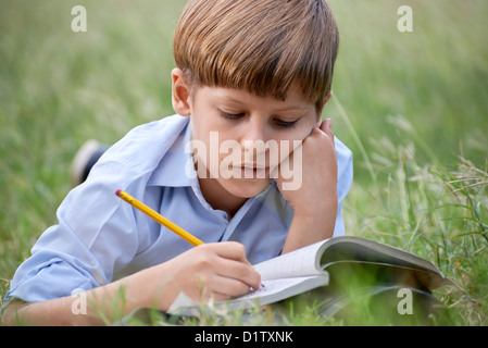 Young people and education, school child doing homework, laying down on grass at park and studying with book. Medium - Stock Photo