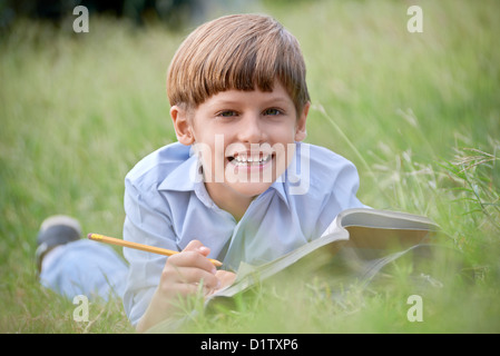 Young people and education, school child doing homework, laying down on grass at park and studying with book, smiling - Stock Photo