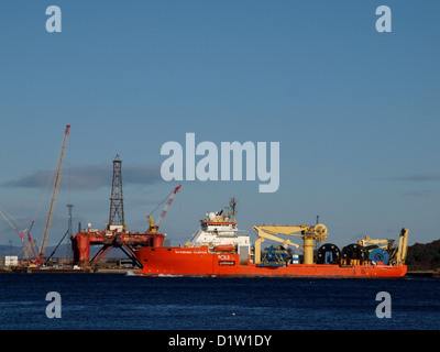 A North Sea construction vessel pass the Nigg Energy Park, with an oil rig in the dry dock, on route to Invergordon - Stock Photo
