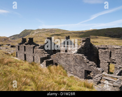 Old ruins of Rhosydd slate quarry quarrymen's barracks with Cnict mountain in Snowdonia National Park near Croesor - Stock Photo