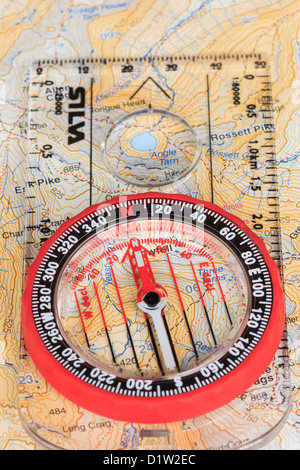 Orienteering compass needle pointing north with grid lines on a Harvey's 1:40000 hiking map and baseplate arrow - Stock Photo