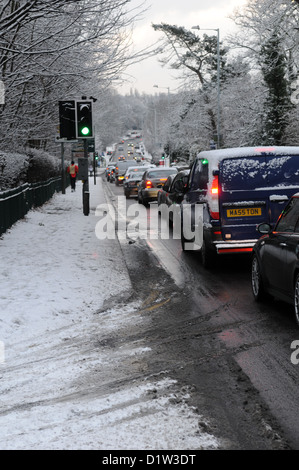 Rush hour traffic queuing on an icy snowy winter road with cars with headlights on on the A41 in Tettenhall, Wolverhampton, - Stock Photo