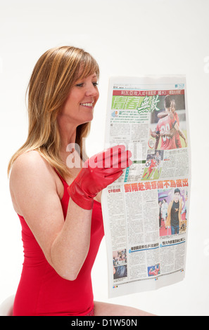 Woman wearing red gloves holding the sports & news section of the Sing Tao Daily the European edition of a Chinese - Stock Photo