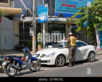 Thailand police officer issuing a traffic ticket for illegal parking. Thailand Southeast Asia - Stock Photo