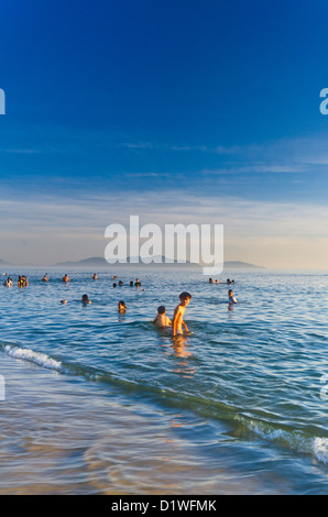 Local people swimming in sea before sun gets to hot, Cua Dai Beach, Hoi An, Vietnam, Asia - Stock Photo