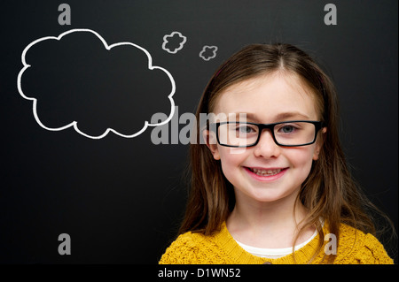 Smart young girl wearing a yellow jumper and glasses stood infront of a blackboard with a drawn on chalk thought - Stock Photo