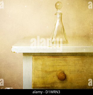 Glass perfume bottle is sitting on top of a bureau in a bedroom - Stock Photo