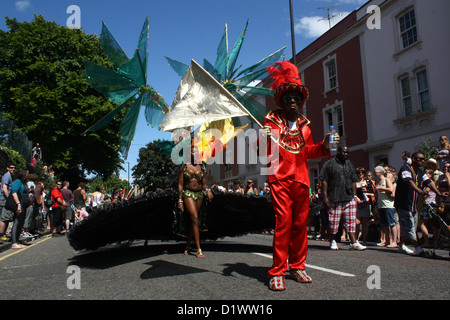 Carnival performers parade down a sun-lit street. A man in a red top hat and suit looks towards camera. - Stock Photo
