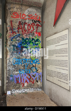 Graffiti on a section of original wall with information in four languages outside Checkpoint Charlie Museum in Berlin - Stock Photo