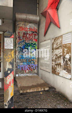 Graffiti on a section of original wall with information, red star and a GDR border post outside Checkpoint Charlie - Stock Photo