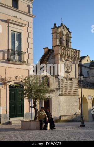 Old men talking in main square in Matera, town, Basilicata region, Southern Italy. Chiesa Materdomini and Spirito Santo Sassi.