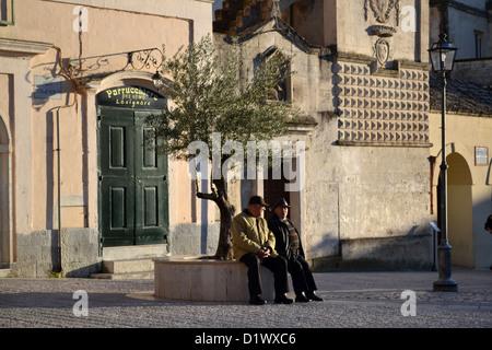 Old men talking in main square in Matera, town, Basilicata region, Southern Italy.
