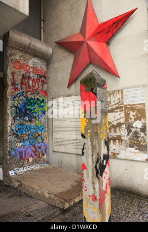 Graffiti on a section of the wall with information, red star and an original GDR border post outside Checkpoint - Stock Photo