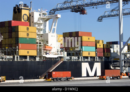 Container ship being loaded at Rotterdam sea port. - Stock Photo