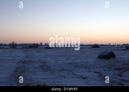 sun setting over rural snow covered scene in remote village of Forget Saskatchewan Canada - Stock Photo
