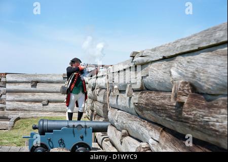 Fort Stanwix reenactors: American Continental Artillery soldier firing musket behind fort walls. - Stock Photo