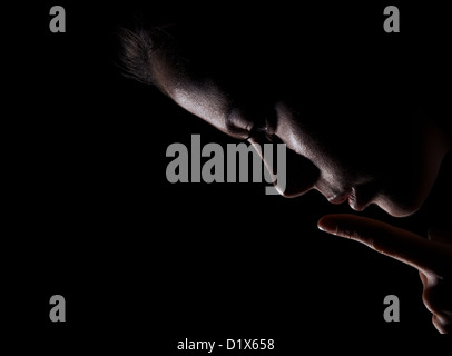 Young Woman looks down and Gesturing For Being Quiet, Shows Silence Sign In Dark Background - Stock Photo