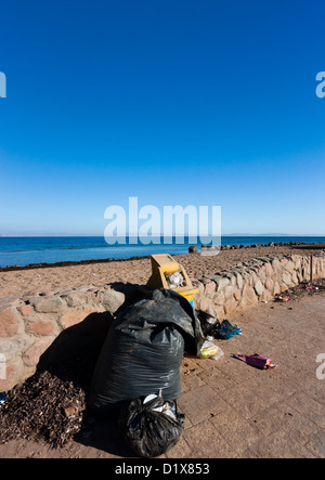Overflowing abandoned bins and garbage bags left next to a tropical beach - Stock Photo