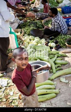 Poor young Indian street boy carrying pots in front of a street market. Andhra Pradesh, India - Stock Photo