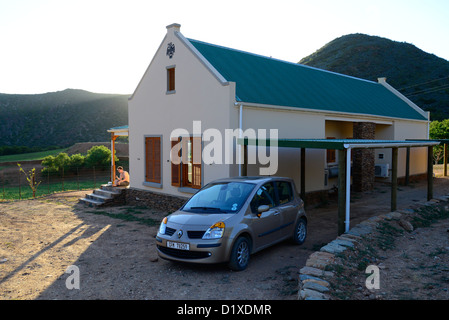 Cream cottage with green roof, car in foreground, mountains at sunset in the Klein Karoo, South Africa - Stock Photo