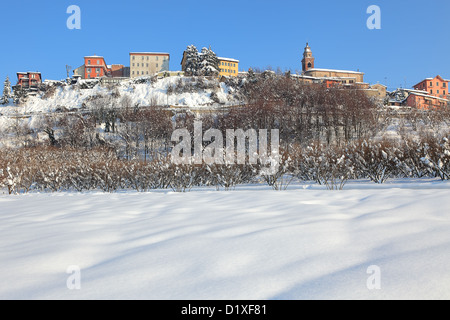 Rural field covered by white snow and small town with colorful houses on the hill on background under blue winter - Stock Photo