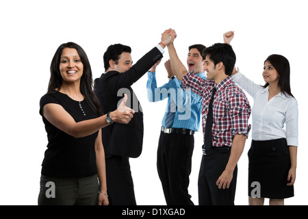 Portrait of a businesswoman showing thumbs up sign and her colleagues cheering in the background - Stock Photo