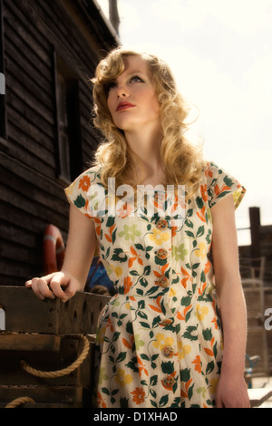 Young blonde woman in vintage print dress leaning against stack of wooden oyster trays with rope handles in sunlit - Stock Photo