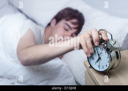 Close up of an old fashioned alarm clock, young man turning it off still half asleep. - Stock Photo