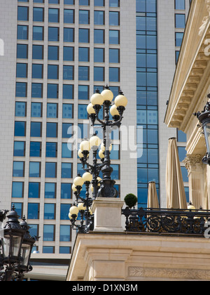Frankfurt am Main, Hesse, Germany. Ornamental lamps of the opera house, the Alte Oper, dwarfed by modern skyscraper, - Stock Photo