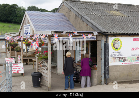 Smithills Open Farm near Bolton. Two women and a child in a buggy at the farm entrance ticket office. - Stock Photo