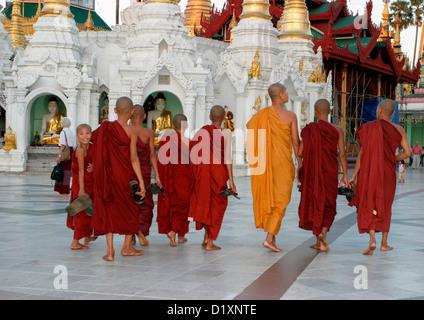 Buddhist monks stroll around Shwedagon Pagoda at dusk in Rangoon, (Yangon), Burma, (Myanmar), Southeast Asia. - Stock Photo