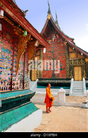 Buddhist monk at La Chapelle Rouge at Wat Xieng Thong in Luang Prabang, Northern Laos, Southeast Asia. - Stock Photo
