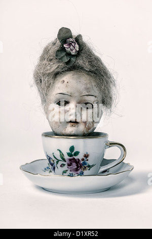 head of a very old, victorian doll in a tea cup - Stock Photo