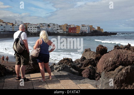 Seaside dreaming. Couple look across bay, Puerto de la Cruz, Tenerife, Canary Islands. - Stock Photo